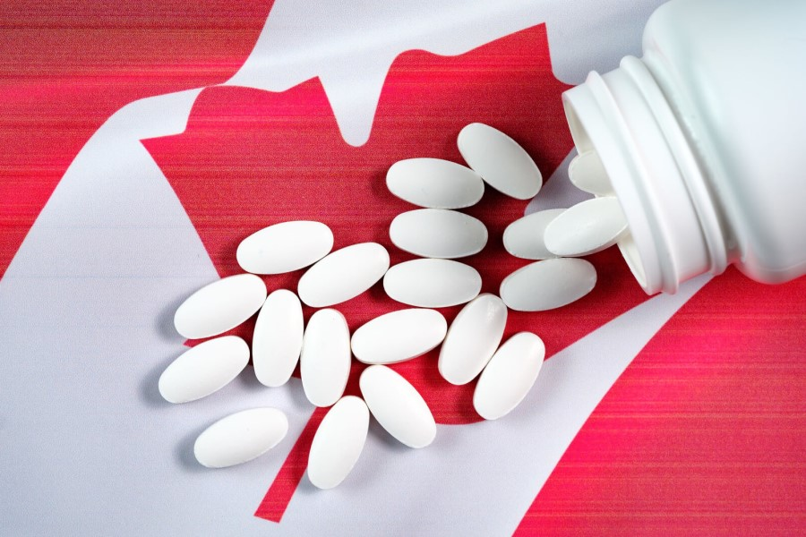 An opened jar of pills and white pills are on the Canadian flag