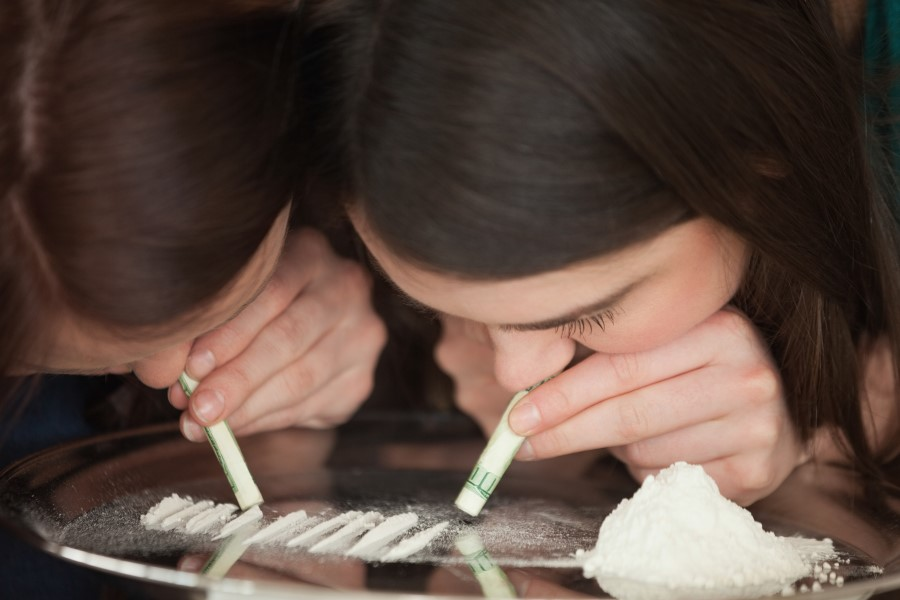Two young girls are snorting illegal white powdered drugs