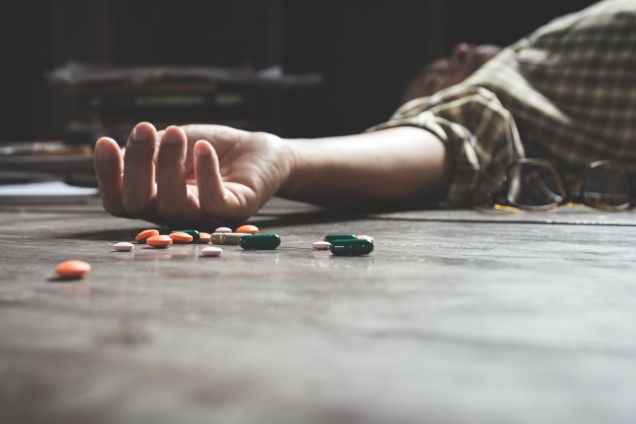 Man is lying down next to the pills after committing suicide